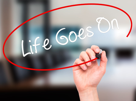 Man Hand writing Life Goes On with black marker on visual screen. Isolated on office. Business, technology, internet concept. Stock Photo