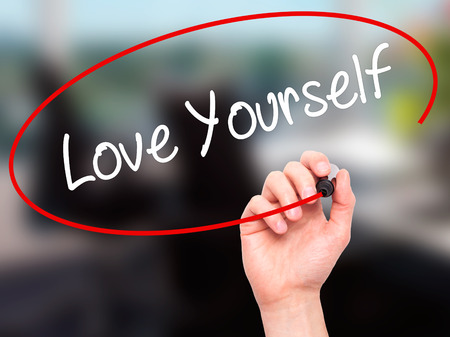 egoistic: Man Hand writing Love Yourself with black marker on visual screen. Isolated on office. Business, technology, internet concept. Stock Photo