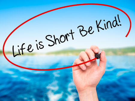 gentleness: Man Hand writing Life is Short Be Kind! with black marker on visual screen. Isolated on nature. Business, technology, internet concept. Stock Photo