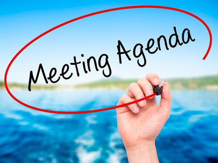 meeting agenda: Man Hand writing Meeting Agenda  with black marker on visual screen. Isolated on nature. Business, technology, internet concept. Stock Photo