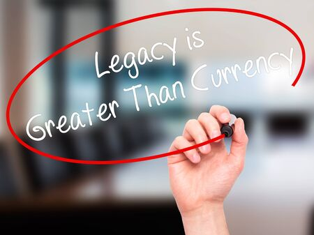 personal contribution: Man Hand writing Legacy is Greater Than Currency with black marker on visual screen. Isolated on background. Business, technology, internet concept. Stock Photo
