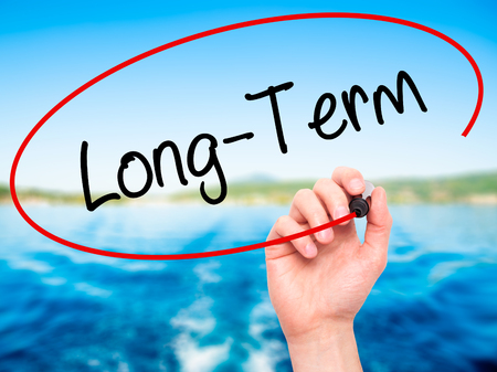 Man Hand writing Long-Term with black marker on visual screen. Isolated on nature. Business, technology, internet concept. Stock Photo