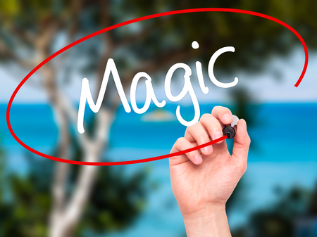 innovator: Man Hand writing Magic with black marker on visual screen. Isolated on background. Business, technology, internet concept. Stock Photo