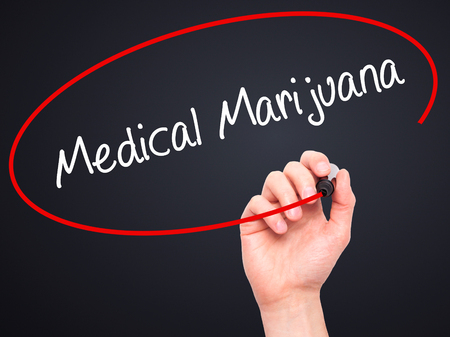 legislators: Man Hand writing  Medical Marijuana with black marker on visual screen. Isolated on black. Business, technology, internet concept. Stock Photo Stock Photo