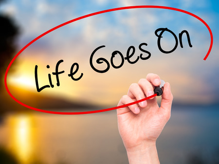 Man Hand writing Life Goes On with black marker on visual screen. Isolated on nature. Business, technology, internet concept. Stock Photo