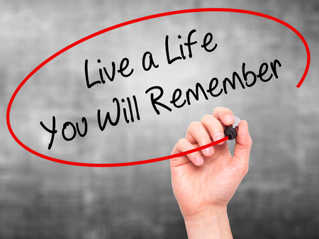 Man Hand writing Live a Life You Will Remember with black marker on visual screen. Isolated on grey. Business, technology, internet concept.