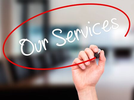 our: Man Hand writing Our Services with black marker on visual screen. Isolated on office. Business, technology, internet concept. Stock Photo Stock Photo