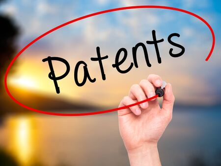 patents: Man Hand writing Patents with black marker on visual screen. Isolated on background. Business, technology, internet concept. Stock Photo
