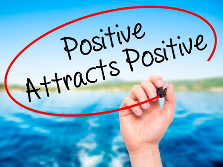 positiveness: Man Hand writing Positive Attracts Positive with black marker on visual screen. Isolated on background. Business, technology, internet concept. Stock Photo Stock Photo