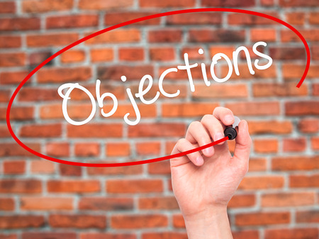 objections: Man Hand writing Objections  with black marker on visual screen. Isolated on bricks. Business, technology, internet concept. Stock Photo Stock Photo