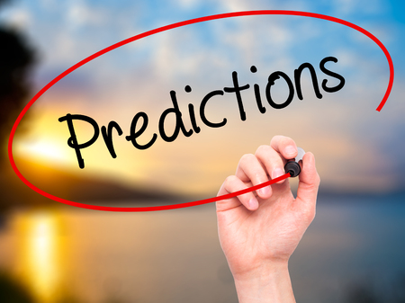 stock predictions: Man Hand writing Predictions  with black marker on visual screen. Isolated on background. Business, technology, internet concept. Stock Photo Stock Photo