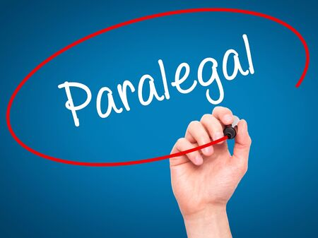 paralegal: Man Hand writing Paralegal with black marker on visual screen. Isolated on blue. Business, technology, internet concept. Stock Photo Stock Photo