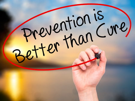cure prevention: Man Hand writing Prevention is Better than Cure with black marker on visual screen. Isolated on nature. Business, technology, internet concept. Stock Image