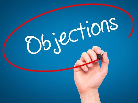 objections: Man Hand writing Objections  with black marker on visual screen. Isolated on blue. Business, technology, internet concept. Stock Photo Stock Photo