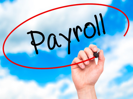 payroll: Man Hand writing Payroll with black marker on visual screen. Isolated on sky. Business, technology, internet concept. Stock Photo Stock Photo