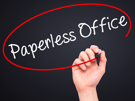 paperless: Man Hand writing Paperless Office  with black marker on visual screen. Isolated on black. Business, technology, internet concept. Stock Photo