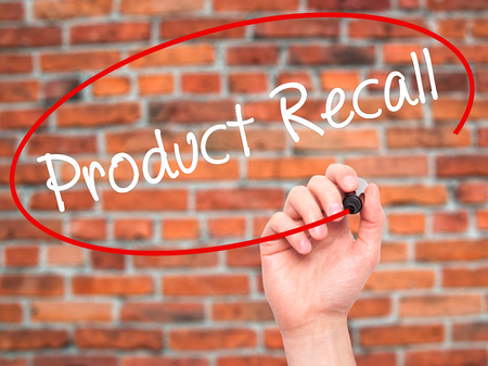 recall: Man Hand writing Product Recall with black marker on visual screen. Isolated on bricks. Business, technology, internet concept. Stock Photo Stock Photo