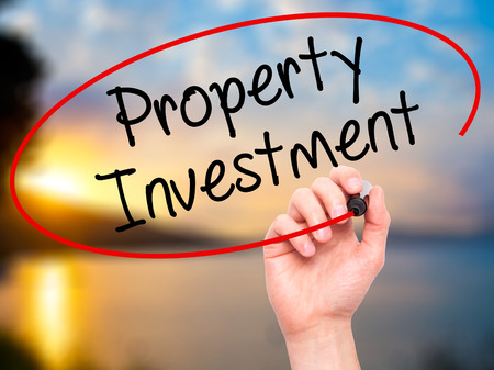 press agent: Man Hand writing Property Investment with black marker on visual screen. Isolated on nature. Business, technology, internet concept. Stock Photo Stock Photo