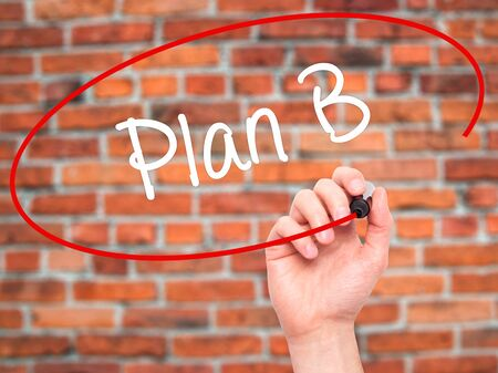 jargon: Man Hand writing Plan B with black marker on visual screen. Isolated on bricks. Business, technology, internet concept. Stock Photo