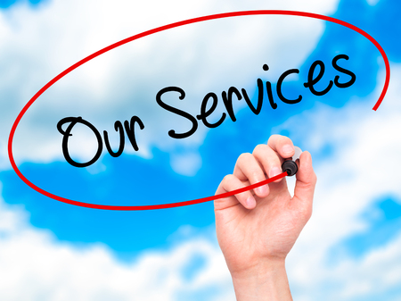 our: Man Hand writing Our Services with black marker on visual screen. Isolated on sky. Business, technology, internet concept. Stock Photo