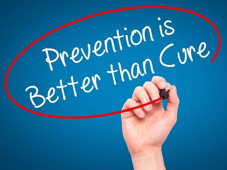 cure prevention: Man Hand writing Prevention is Better than Cure with black marker on visual screen. Isolated on blue. Business, technology, internet concept. Stock Photo Stock Photo