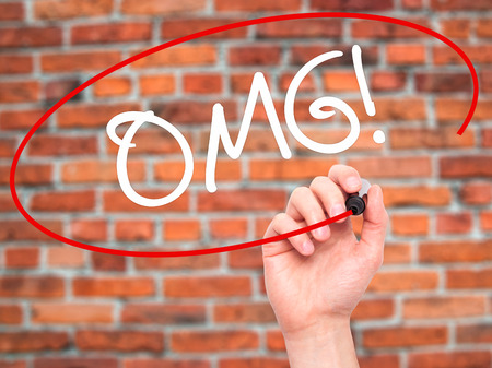 gosh: Man Hand writing OMG (Oh My God) with black marker on visual screen. Isolated on bricks. Business, technology, internet concept. Stock Photo