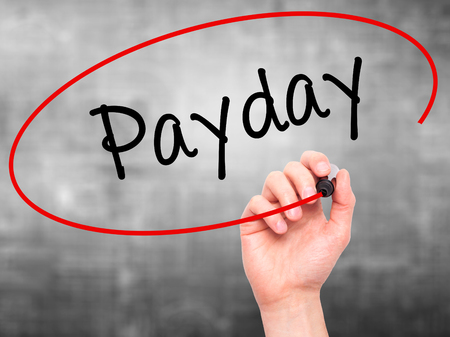 payday: Man Hand writing Payday   with black marker on visual screen. Isolated on grey. Business, technology, internet concept. Stock Photo Stock Photo