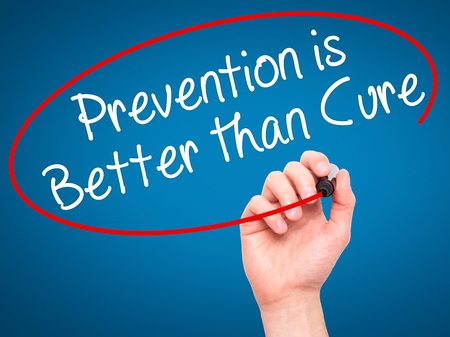 cure prevention: Man Hand writing Prevention is Better than Cure with black marker on visual screen. Isolated on blue. Business, technology, internet concept. Stock Image Stock Photo