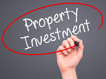 press agent: Man Hand writing Property Investment with black marker on visual screen. Isolated on grey. Business, technology, internet concept. Stock Photo