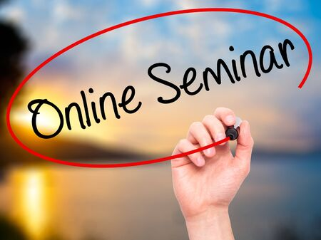 elearn: Man Hand writing Online Seminar with black marker on visual screen. Isolated on nature. Business, technology, internet concept. Stock Photo