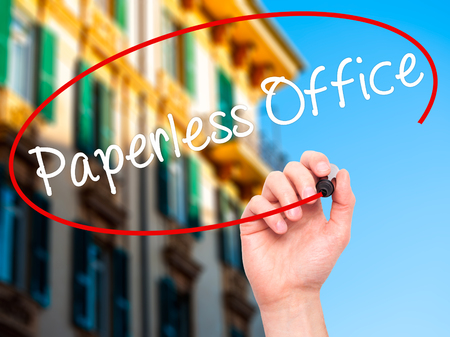 paperless: Man Hand writing Paperless Office  with black marker on visual screen. Isolated on city. Business, technology, internet concept. Stock Photo Stock Photo