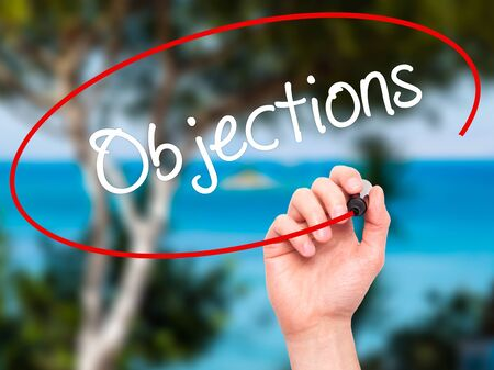 affirmative: Man Hand writing Objections  with black marker on visual screen. Isolated on nature. Business, technology, internet concept. Stock Photo