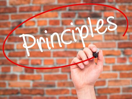 principles: Man Hand writing Principles with black marker on visual screen. Isolated on bricks. Business, technology, internet concept. Stock Photo Stock Photo