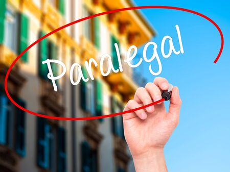 paralegal: Man Hand writing Paralegal with black marker on visual screen. Isolated on city. Business, technology, internet concept. Stock Photo Stock Photo