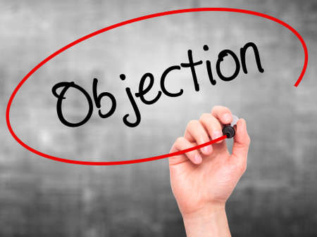 objection: Man Hand writing Objection with black marker on visual screen. Isolated on background. Business, technology, internet concept. Stock Photo