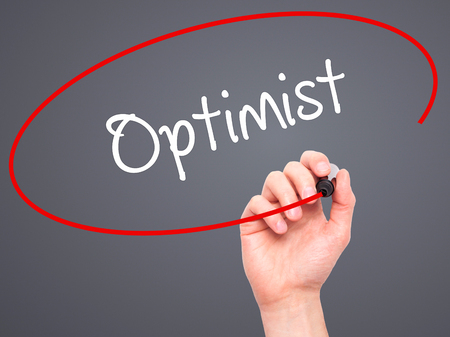 and an optimist: Man Hand writing Optimist  with black marker on visual screen. Isolated on grey. Business, technology, internet concept. Stock Photo Stock Photo