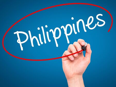 underdeveloped: Man Hand writing Philippines with black marker on visual screen. Isolated on blue. Business, technology, internet concept. Stock Photo Stock Photo