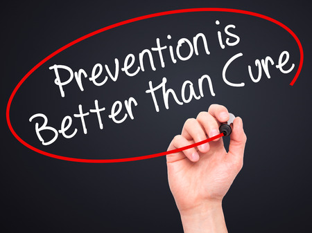 cure prevention: Man Hand writing Prevention is Better than Cure with black marker on visual screen. Isolated on black. Business, technology, internet concept. Stock Image