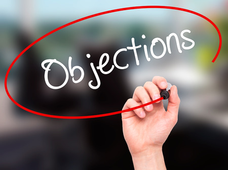 persuasive: Man Hand writing Objections  with black marker on visual screen. Isolated on office. Business, technology, internet concept. Stock Photo