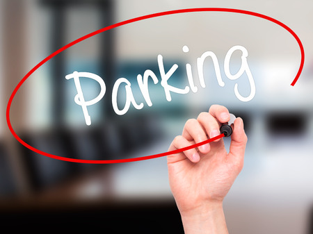 visual screen: Man Hand writing Parking with black marker on visual screen. Isolated on office. Business, technology, internet concept. Stock Photo