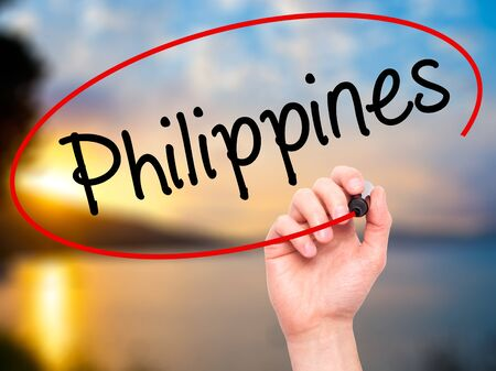 underdeveloped: Man Hand writing Philippines with black marker on visual screen. Isolated on nature. Business, technology, internet concept. Stock Photo