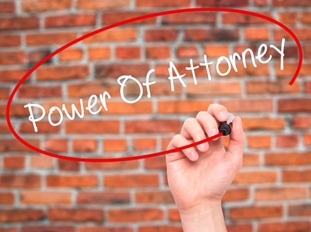 deeds: Man Hand writing Power Of Attorney with black marker on visual screen. Isolated on bricks. Business, technology, internet concept. Stock Photo