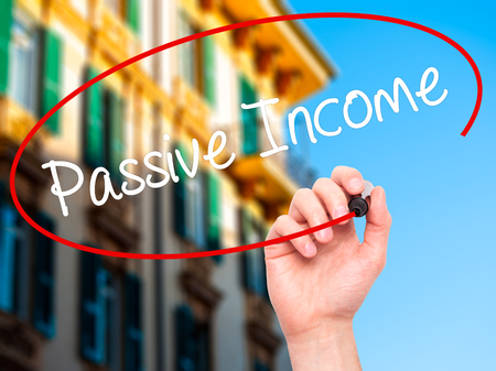 passive income: Man Hand writing Passive Income with black marker on visual screen. Isolated on city. Business, technology, internet concept. Stock Photo Stock Photo
