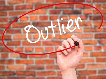 oddity: Man Hand writing Outlier  with black marker on visual screen. Isolated on background. Business, technology, internet concept. Stock Photo Stock Photo