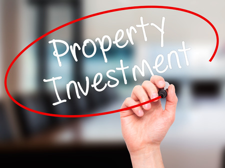 press agent: Man Hand writing Property Investment with black marker on visual screen. Isolated on office. Business, technology, internet concept. Stock Photo