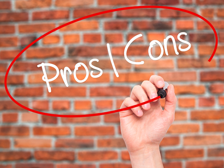 pros: Man Hand writing Pros  Cons with black marker on visual screen. Isolated on bricks. Business, technology, internet concept.
