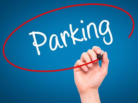 multi story car park: Man Hand writing Parking with black marker on visual screen. Isolated on blue. Business, technology, internet concept. Stock Photo
