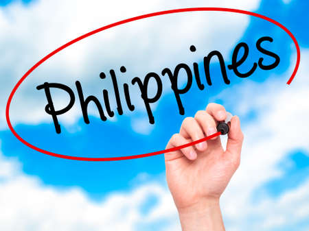 underdeveloped: Man Hand writing Philippines with black marker on visual screen. Isolated on sky. Business, technology, internet concept. Stock Photo Stock Photo