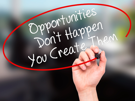 street wise: Man Hand writing Opportunities Dont Happen You Create Them with black marker on visual screen. Isolated on background. Business, technology, internet concept. Stock Photo