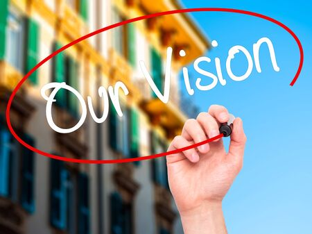 our vision: Man Hand writing Our Vision with black marker on visual screen. Isolated on city. Business, technology, internet concept. Stock Photo